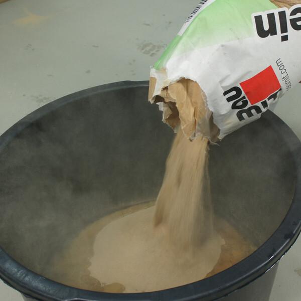 Lehmputz und Wasser in Mörtelkübel geben