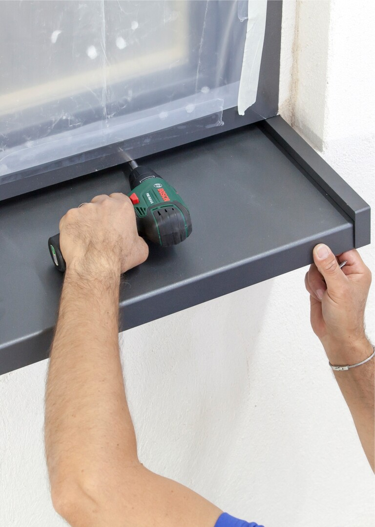 Blech-Fensterbank mit rostfreien Schrauben im Fensterrahmen oder Fensterbankprofil anschrauben.
