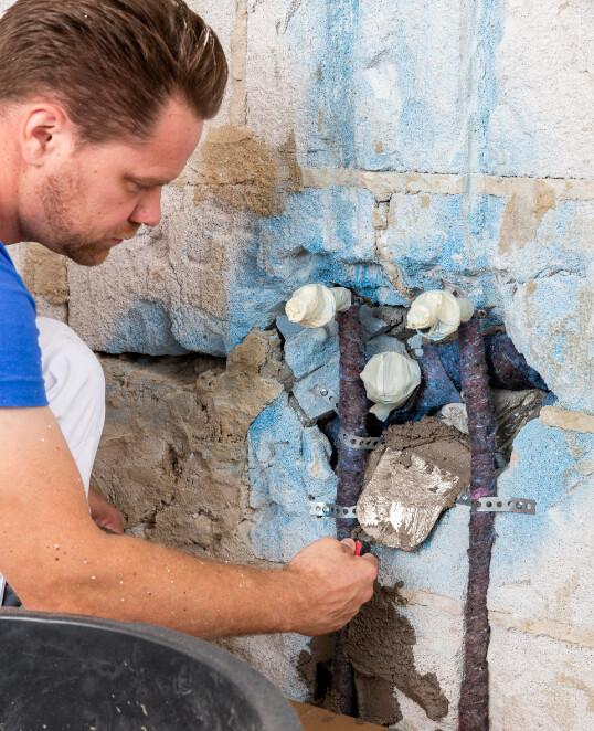 Ausbrüche und tiefe Löcher im Mauerwerk bzw. Ziegelwand mit Schlitz- und Verfüllmörtel verschließen